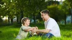 Conversation of father and small son in a summer garden